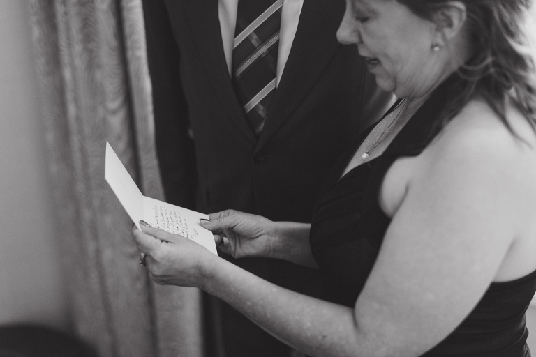groom's parents reading a letter at the fairmont banff springs hotel from nicole sarah, wedding photographer in calgary