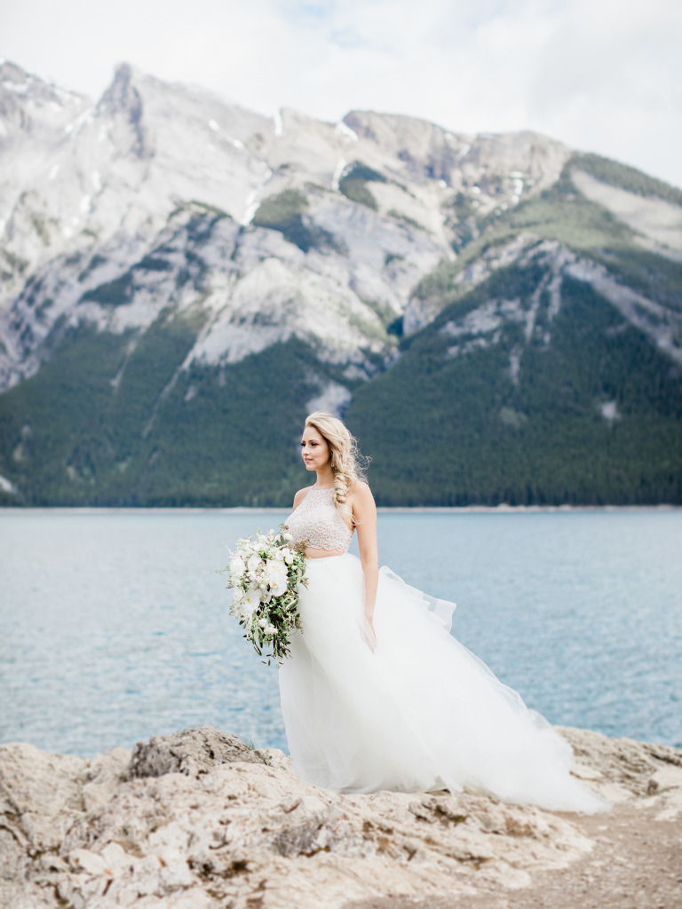 canmore wedding photographer, banff wedding photographer, calgary wedding photographer, crop top wedding dress, mountain wedding, film wedding, outdoor mountain wedding ceremony, large flower bouquet, navy groom suit, sage bridesmaid gowns, groom crying, bridesmaids laughing, bridesmaid inspiration, powder blue bridesmaid gown, two piece bride gown, tulle skirt, watters skirt, theia skirt, beaded crop top, summer wedding, mountainscape wedding, romantic rocky mountain wedding, love in the rockies, tacori oval ring, the mrs. box pink