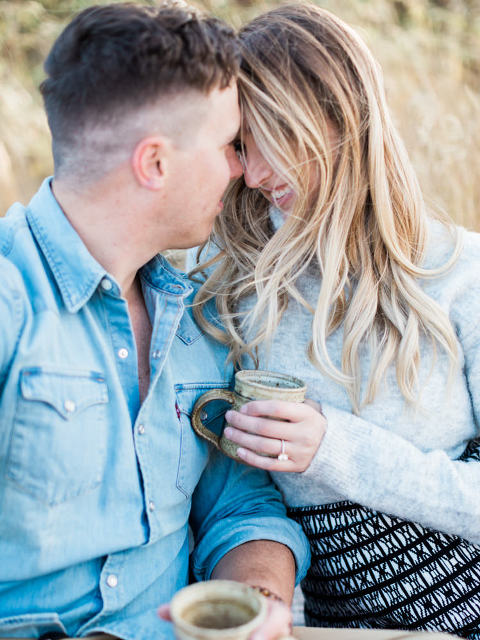 autumn sunset engagement, black floppy hat, black hat engagement, oval wedding ring, oval engagement ring, fall engagement photos, fall engagement ideas, fall engagement poses, fall engagement, film photography, film photographer, style me pretty, cozy autumn engagement, cozy engagement, engagement wardrobe fall, fall engagement clothing, warm sweater photo session, hot chocolate engagement, ring photos, ring goals, engagement rings, sunset photo, camping engagement theme