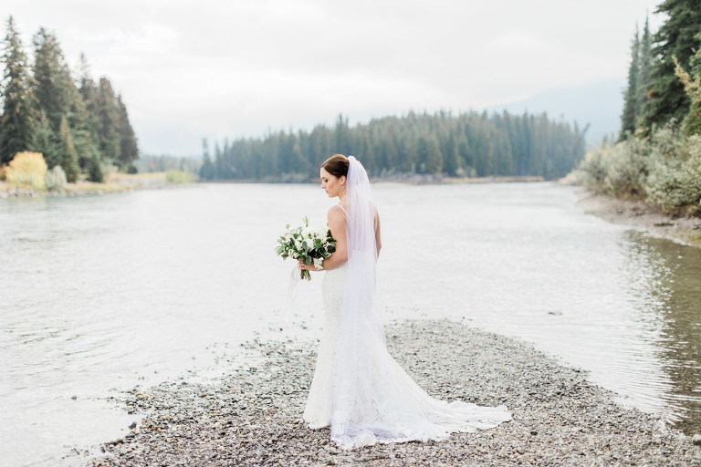 first look inspiration, first look photos, bride groom mountains, bride groom portraits, wedding inspiration, wedding hairstyles, groom tuxedo, groom suit, white and green bouquet, canmore wedding photography, banff wedding photography, mountain photographer, banff wedding, canmore wedding, mountain wedding inspiration, water mountains wedding, gazebo wedding, low cut bridal gown, bride groom poses, nicole sarah photography