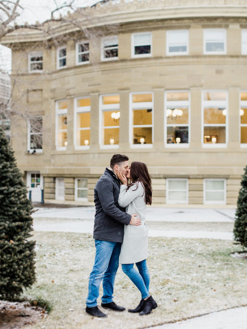winter engagement, winter photos, christmas engagement, engagement ideas, engagement outfit ideas, grey wool coat, wool coat, snow, wintery engagement, getting married,  winter engagement photos outfits, engagement poses, photography poses, romantic poses, how to pose, couple kissing, playing in the snow, nicole sarah, calgary landmarks, calgary christmas, events in calgary, wedding photographers nicole sarah, christmas engagement pictures, xmas engaged, mansion engagement, urban engagement setting, urban backdrop